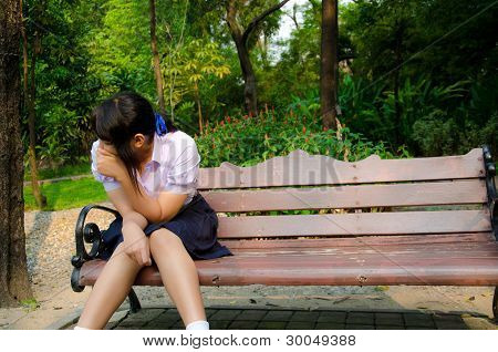 High-schoolgirl Crying Alone On The Bench