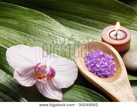 bowl of salt and orchid on leaf