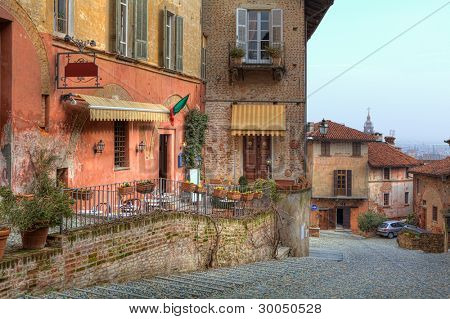 Horizontal image of narrow stone paved street among multicolored houses in town of Saluzzo, Northern Italy.