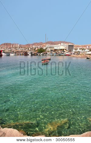 Vertical oriented image of boats floats on water surface against shoreline of popular touristic resort of Eilat in Israel.