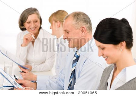 Smiling businessman during meeting with team colleagues