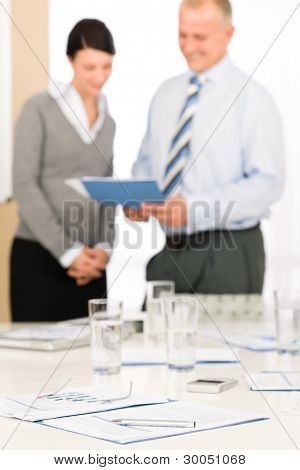Office supply on table - two business people out of focus
