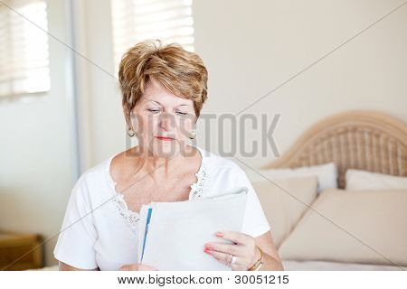 senior woman sitting on bed and reading newspaper