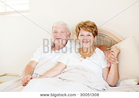happy senior couple holding hands in bed