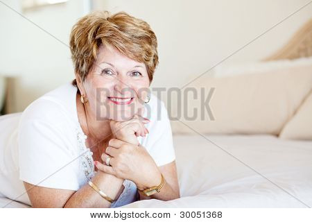 happy senior woman lying on bed