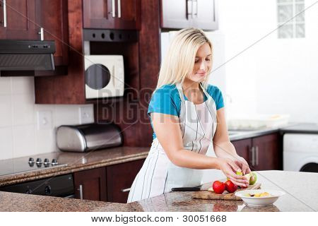 beautiful young european woman making fruit salad in kitchen