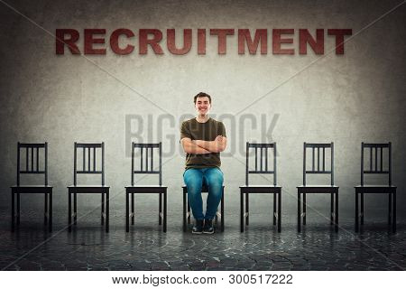 Young Man Sitting On A Chair As Perfect Candidate For A Vacant Job Place Waiting To Be Hired. Busine
