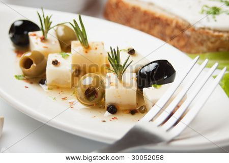 Cheese and olives salad with rosemary and pepper