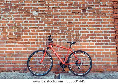 Red City Bike In The Summer In City On A Brick Wall Background. The Concept Of Parking, Bike, Rest I