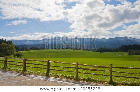 Green Field With Wooden Fence In Bavarian Alps, Germany