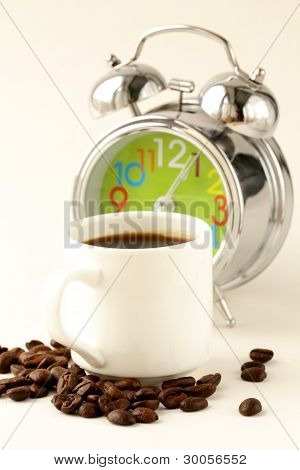 Alarm clock and white coffee cup