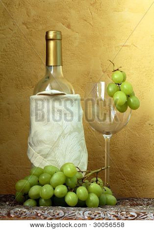 still life of wine bottles, glass and green grapes for vintage table
