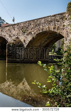Along The Quays Under An Old Vaulted Bridge In A French Province In Semur En Auxois