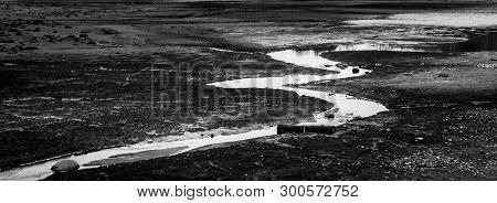 Abstract And Conceptual Watercourse On A Desert Land In Black And White
