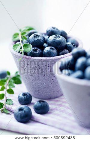 Fresh blueberries in purple bowls