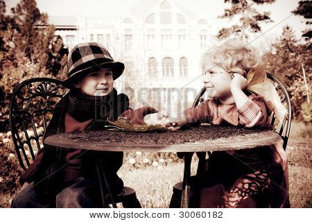 Cute children having a rest at a park. Retro style.