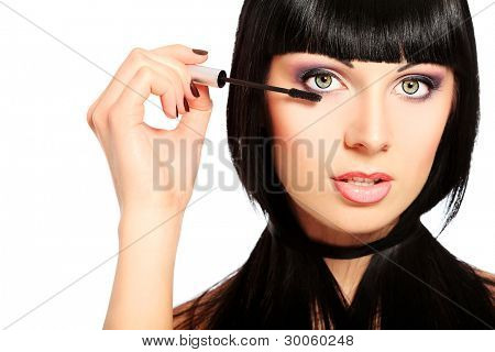 Beautiful young woman posing with mascara. Isolated over white.