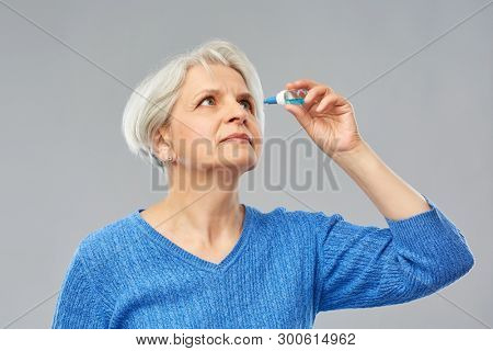 medicine, health and vision people concept - portrait of senior woman with dry eye syndrome using drops over grey background