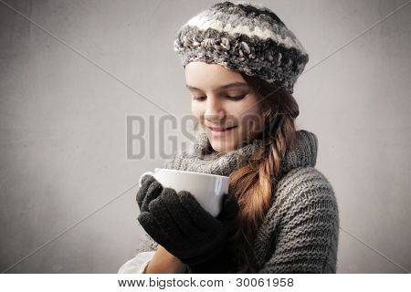Smiling teenage gild in warm clothes holding a bowl of hot drink