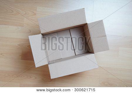 Topview Of Empty Cardboard Box On Laminate Floor