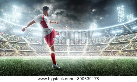 Soccer Action. Professional Soccer Player Kicks A Ball On The Night Soccer Stadium With Fans And Fla