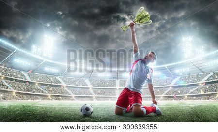 Soccer Player Celebrates Winning The Open Stadium. Soccer Player Holds A Trophy One Hand . Medal On