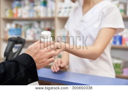 Pharmacist Working With Customers In Pharmacy At Counter. Woman Giving To Client Medicaments. Man Bu