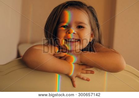 An Attractive Child Is Standing In A Cozy Room And Smiling, A Rainbow Hits The Face, Creating An Unu