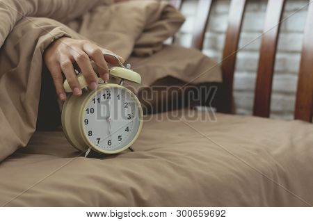 Alarm Clock With Lazy Woman Hand Put On For Stop Alarm Clock To Snooze From Wake Up On Bed In Bedroo