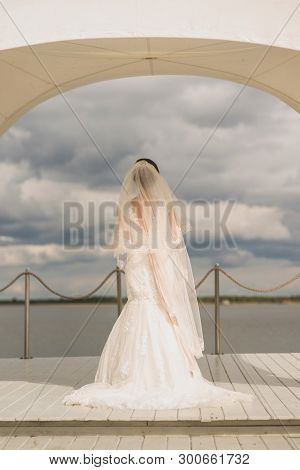 The Bride In A Beautiful White Lace Dress With A Veil On Her Head Stands On A Light Colored Wooden P