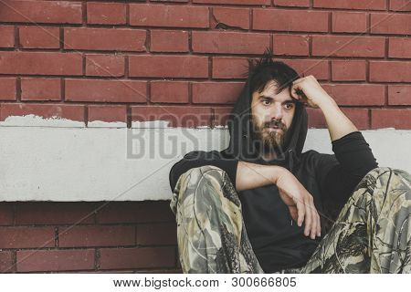 Homeless Man, Homeless Man Drug And Alcohol Addict Sitting Alone And Depressed On The Street Leaning