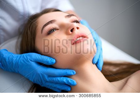 Beautician Hands In Gloves Touching Face Of Attractive Woman. Facial Beauty. Beautiful Young Female