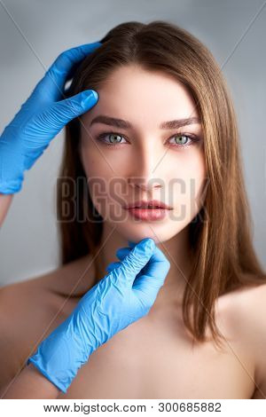 Beautician Doctors Hands In Gloves Touching Face Of Attractive Woman. Fashion Blonde Model After Cos