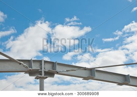 Part Of The Metal Frame Of The Building Of Galvanized Metal Against The Blue Sky With Clouds. Proces