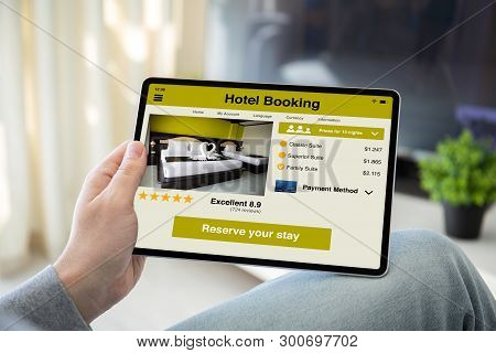 Man Hands Holding Computer Tablet With App Hotel Booking On The Screen In The Home Room