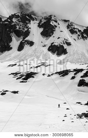 High mountain with snow cornice and avalanche trail, snowy plateau and small silhouette of hiker at sunny day. Turkey, Kachkar Mountains, highest part of Pontic Mountains. Black and white toned landscape. poster