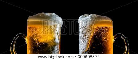 Two Large Glasses Of Beer With Foam Close-up, Facing Each Other, Isolated Against A Black Background
