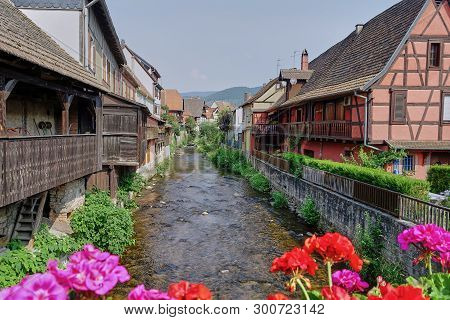 Riquewihr, Alsace, France - Aug 2015: Quaint Medieval Village With River Running Through It In The A