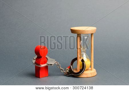 The Red Figure Of A Man Is Handcuffed To An Hourglass. Dependence, There Is Little Time Left. Stream