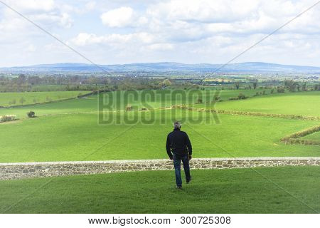Middle-aged Man With Dark Clothes, Walking Across A Field, Before To Jump A Wall, A Stone Fence. Ove
