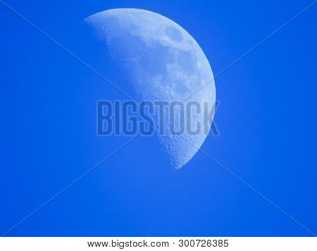 The Crescent Moon In The Blue Afternoon Sky