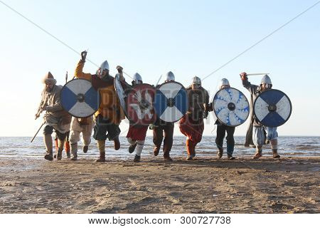 Slavic Warriors Reenactors With Wearpons And Shields Training Fighting Outdoors At Seaside , Running