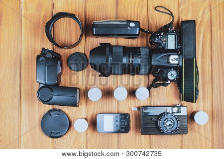Different Generations Of Cameras And Flash With Synchronizer On The Background Of Wooden Boards