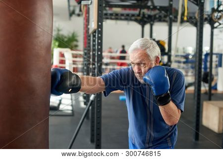 Male Pensioner Trains On A Punching Bag. Serious Older Man Working Out With Punching Bag At Boxing H