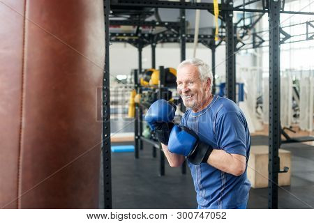 Handsome Senior Male Training With Punching Bag. Old Trainer Training With Punching Bag In Fitness S