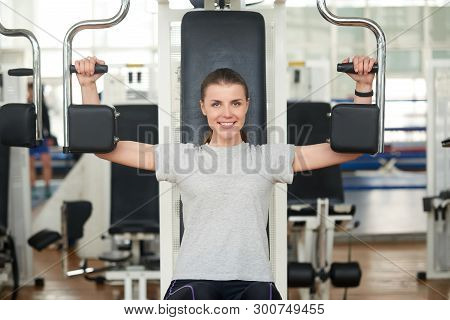 Woman On Shoulder Press Machine In Fitness Club. Smiling Caucasian Woman Looking At The Camera While