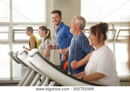 Handsome Man On Treadmill Looking At Camera. Group Of People Working Out At Fitness Club. Sport, Fit