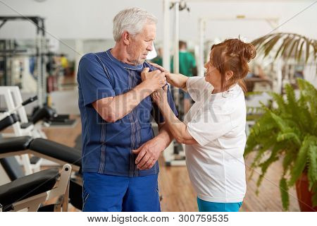 Senior Man Suffering From Shoulder Pain At Gym. Elderly Man Injured Shoulder During Workout. People,