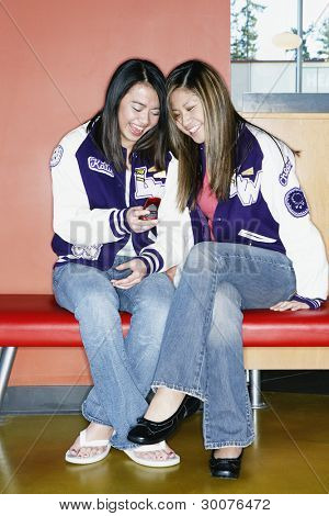Two teenage girls wearing letterman's jackets with cell phone