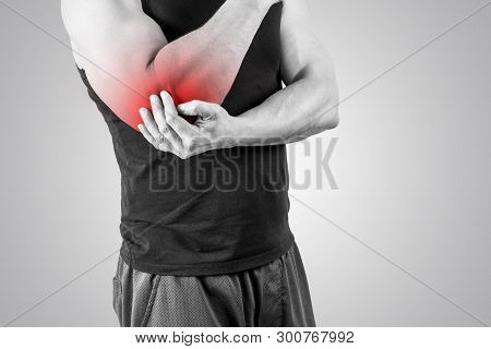 Muscle Man Holds His Injured Elbow. Red Color Is Pain